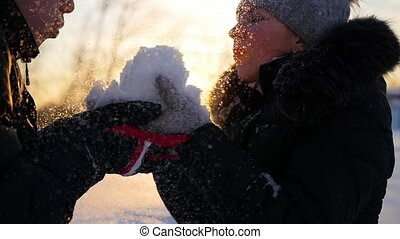 girl and guy blows snow with hands on sunset background