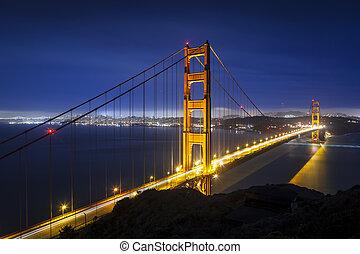 Golden Gate Bridge in San Francisco, California at night with traffic light trails.