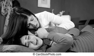 Woman comforting sad girlfriend in bed after breakup black and white