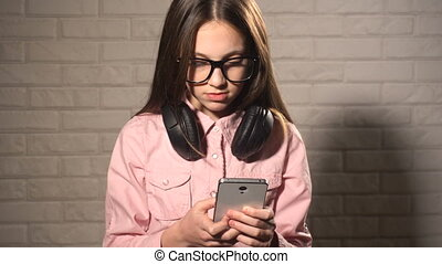Teen girl messaging in smartphone - Teen girl in headphones...
