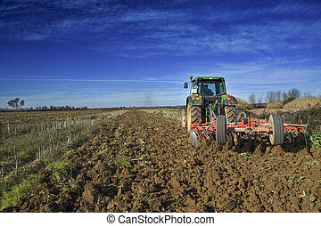 Agriculture landscape with Farm tractor preparing the soil -...