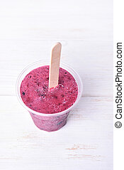Blackcurrant popsicle made in plastic cup on white wooden...