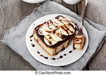 Banana cheese cake with chocolate syrup and piece of fruits