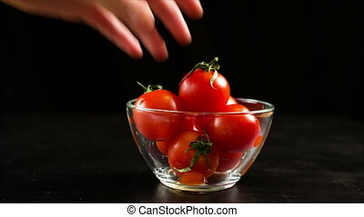 Picking up one cherry tomato from glass bowl on black...
