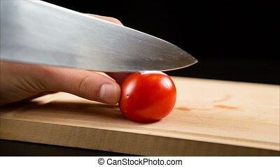 Cutting one red cherry tomatoes on wooden cutting board -...