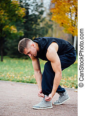 Fitness man tie shoelaces in the fall park.