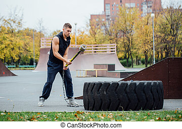 Fitness sport man workout outdoor. with hammer and tractor tire.