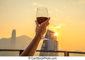 Rooftop drink enjoy - Close up of glass of red wine raised...