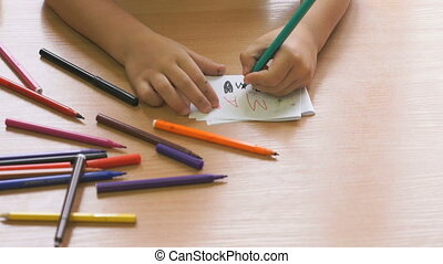 Child draws the picture using the felt pens - Child sitting...