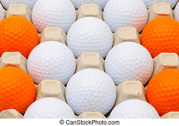 White and orange golf balls in the box for eggs