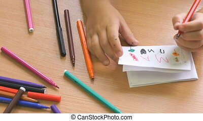 Child draws the picture using the felt pens