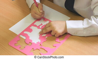 Child draws the picture using a felt pen. Close-up