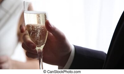 groom with champagne glass close up in daylight