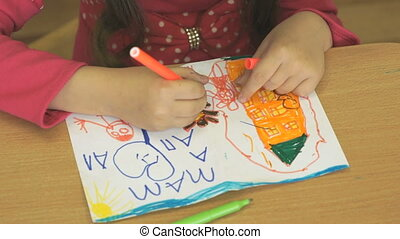 Kid draws image using the markers. Close-up - Kid sitting at...