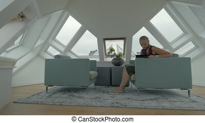 Woman in Cube House spending free time with tablet computer...
