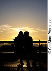Romantic silhouette of couple sitting with sunset and city in the background