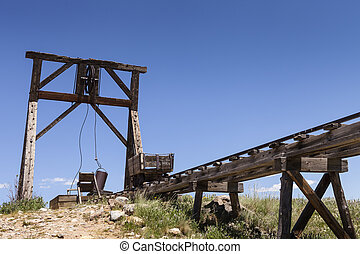 Old mining ore cart on trestle with head frame under blue...
