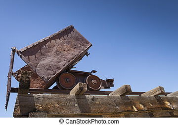 Old rusty mining ore cart on trestle under blue sky.