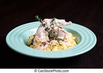 Stewed rabbit meat in creamy sauce with herbs and couscous....