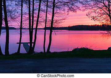 Sunset on a lake landscape with trees