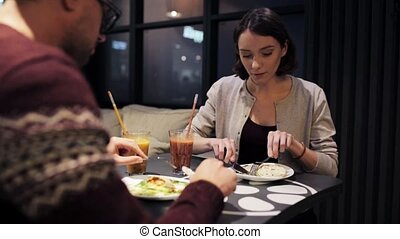 happy couple enjoying dinner at vegan restaurant - eating,...
