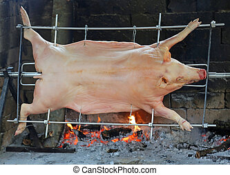 fat pig while it is cooked in huge spit of restaurant