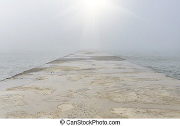 Concrete pier in a foggy day.