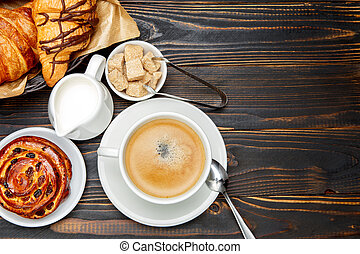 cup of coffe and cinnabon on wooden background