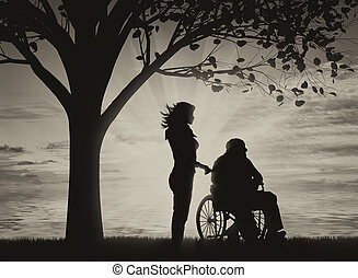 Disabled persons in wheelchair with nurse under tree near see