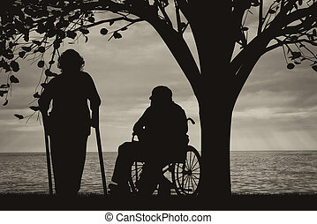 People with disabilities near sea under tree in wheelchair and on crutches