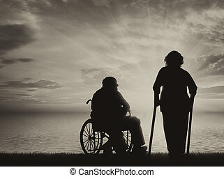 Disabled persons near sea in wheelchair and on crutches
