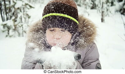 Child blowing snow from his hands slow motion