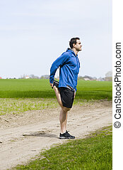man hold his foot at the back - Young male athlete in short...