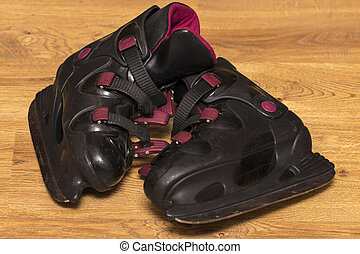Side view black ice skates on wooden background