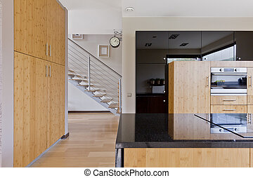 Spacious kitchen with wooden furnitures, kitchen island with...