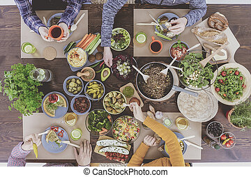 Friends sitting beside rustic table while eating healthy...