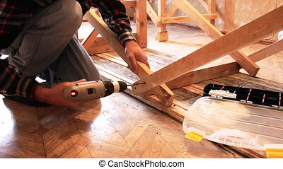 Man Screwing a screw into the wood element by means of the...