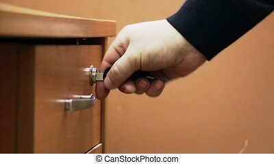 Man Puts it in the drawer business papers - A man opens a...