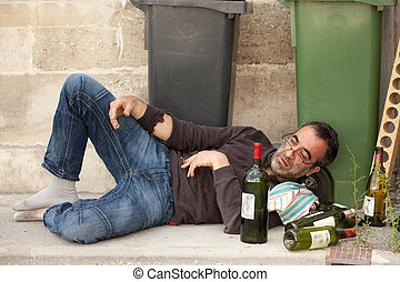 poor man - poor and drunk man lying on sidewalk with bottles...
