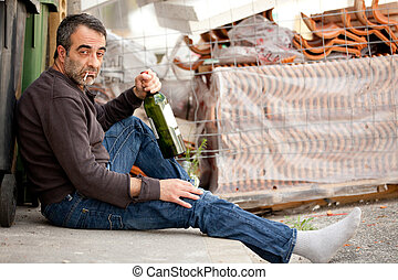 drunk sad man - very sad man drinking wine on sidewalk near...