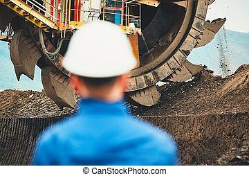 Coal mining in an open pit. Miner looking on the huge...