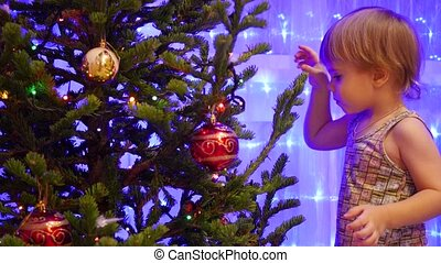 baby decorates Christmas tree Christmas toys - happy baby...