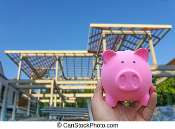 Male hand holding a pink piggy bank on blured construction...