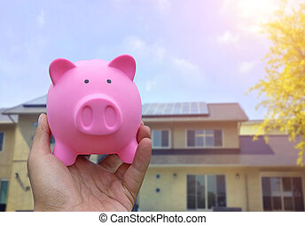 Male hand holding a pink piggy bank on blured house...