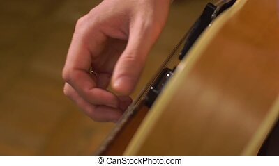 Guitarists hands close-up - Guitarists hands tuning guitar...