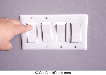 Turning off the lights - A hand turning off a light switch