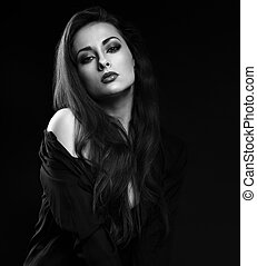 Beautiful brunette female model with long hair posing in black shirt on dark background with red lipstick. Black and white portrait