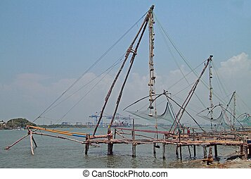 People are walking near chinese fishing nets in Kochi -...