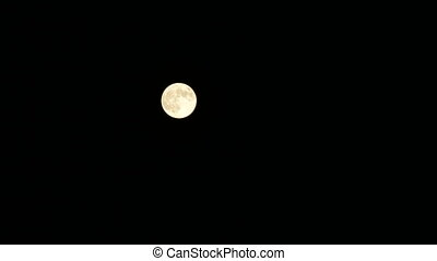 The Moon makes it's way on dark night sky. Bright full planet-satellite of Earth.