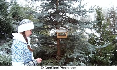 Snow Maiden in forest putting feed in feeder for birds on a firm tree close view